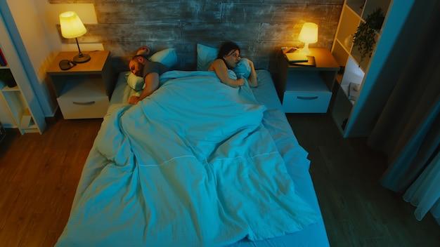 Jeune couple sous les draps n'arrive pas à dormir après une mésentente. clair de lune bleu.