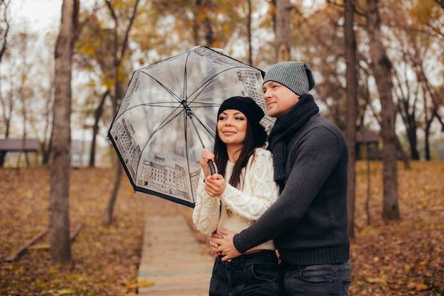 Jeune couple sous un parapluie transparent se cache des intempéries.