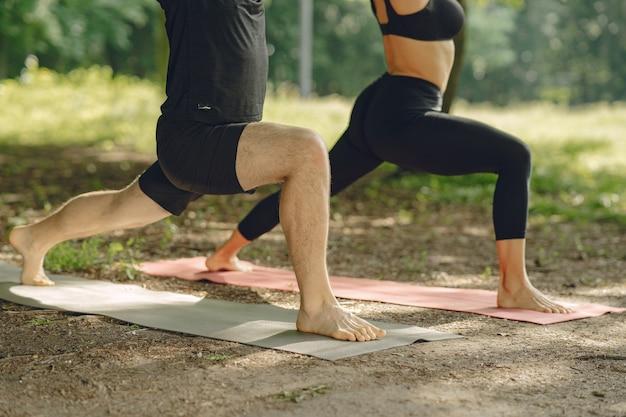 Jeune couple sportif faisant du yoga. les gens dans un parc d'été.