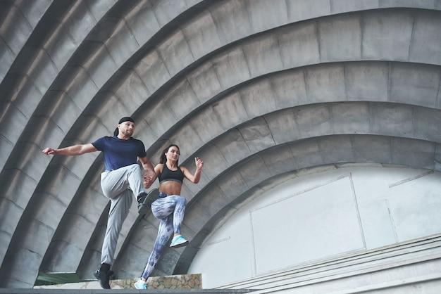 Jeune couple sportif heureux dans la rue de la ville, effectuant le parkour.