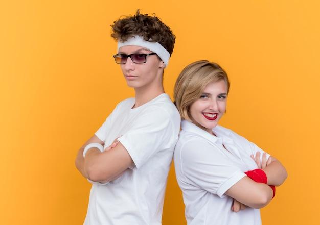 Jeune couple sportif homme et femme à la confiance debout dos à dos sur mur orange