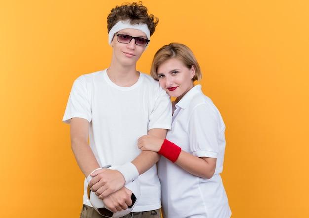 Jeune couple sportif homme et femme debout ensemble tenant un ballon de football souriant sur un mur orange