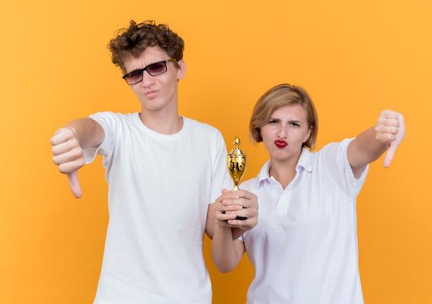 Jeune couple sportif homme et femme debout ensemble tenant le trophée montrant les pouces vers le bas debout sur le mur orange