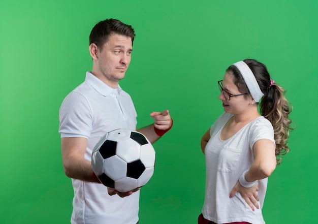 Jeune couple sportif homme sérieux tenant un ballon de football en regardant sa petite amie souriante sur vert