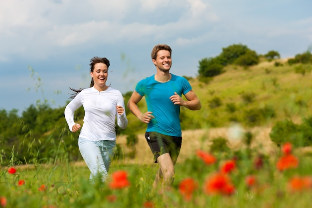 Jeune couple sportif jogging dans la nature
