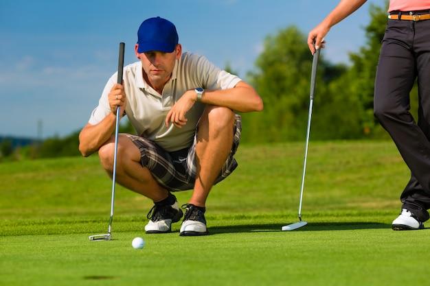 Jeune couple sportif jouant au golf sur un parcours