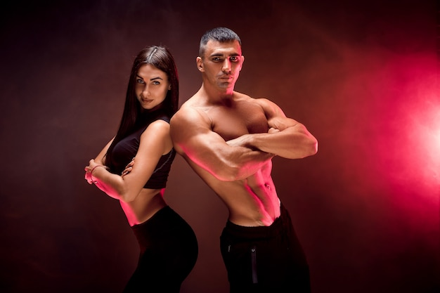 Jeune couple sportif sur mur noir