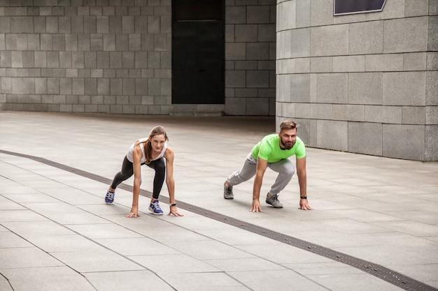 Jeune couple sportif en position de départ prêt à concourir et à courir. à l'aide d'un tracker sportif.
