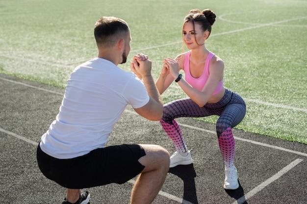 Jeune couple sportif s'entraîne au stade en été au coucher du soleil, s'échauffe et s'accroupit. sport. aptitude