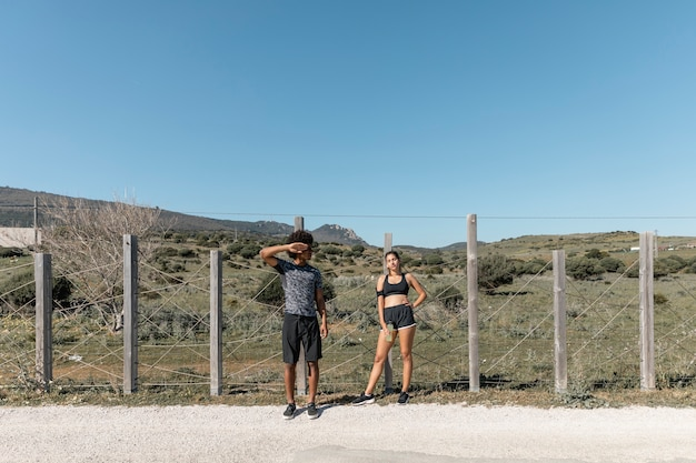 Jeune couple, sportswear, debout, bord route
