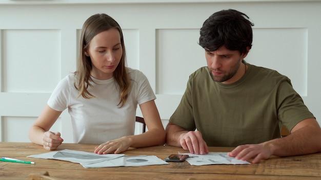 Jeune couple stressé, calcul des dépenses mensuelles à domicile, paiement des factures de carte de crédit.