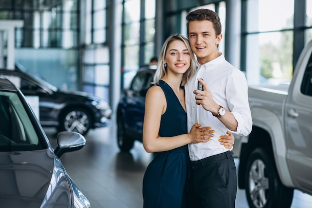 Jeune couple en suivant une voiture dans une salle d'exposition
