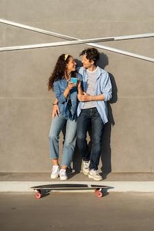 Un jeune couple surfe sur une application de médias sociaux sur un smartphone, regarde une vidéo en ligne à l'extérieur à l'aide d'internet sans fil