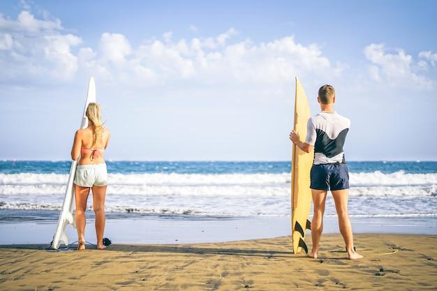 Jeune couple de surfeurs debout sur la plage avec des planches de surf se préparant à surfer sur de hautes vagues