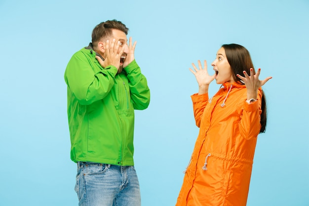 Jeune couple surpris au studio en vestes d'automne isolé sur bleu. émotions négatives humaines. concept du temps froid. concepts de mode féminine et masculine