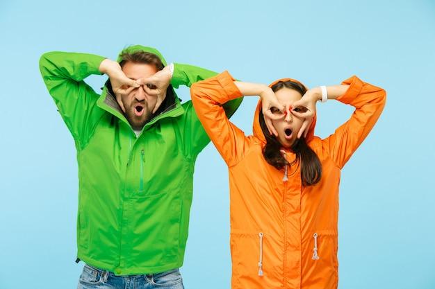 Le jeune couple surpris au studio en vestes d'automne isolé sur bleu. humaines émotions positives heureuses. concept du temps froid. concepts de mode féminine et masculine