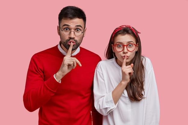 Jeune couple surpris faire signe de silence, se tenir près les uns des autres, garder l'index sur les lèvres, démontrer le geste de taire, demander de ne pas dire secret