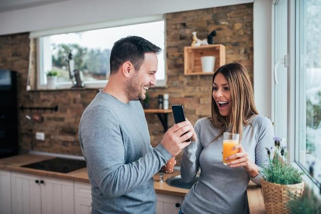 Jeune couple surpris par les bonnes nouvelles du matin dans la cuisine.