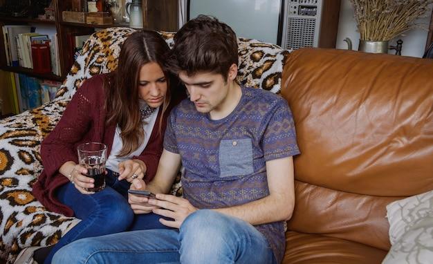 Jeune couple surpris à la recherche d'un smartphone assis sur un canapé à la maison