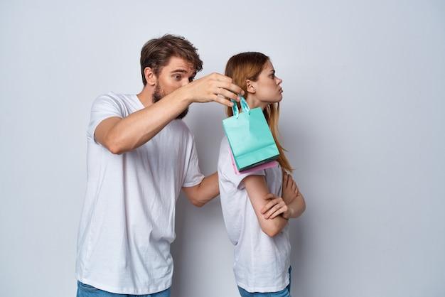 Jeune couple en t-shirts blancs cadeaux vacances émotions amusantes
