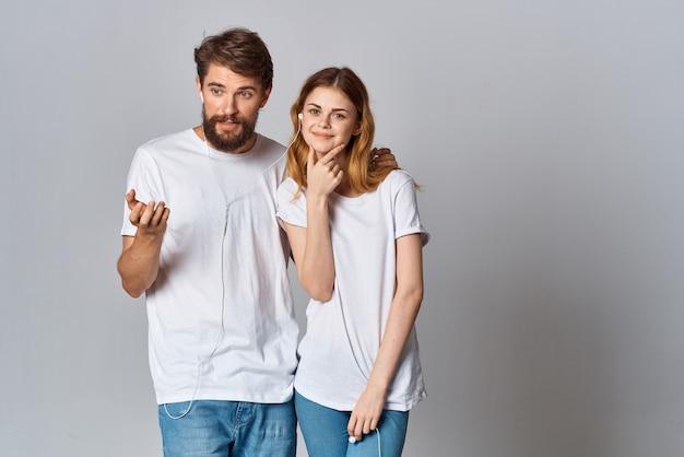 Jeune couple en t-shirts blancs portant des écouteurs écoutant de la musique et des divertissements technologiques