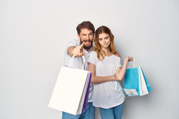 Jeune couple en t-shirts blancs shopping fun