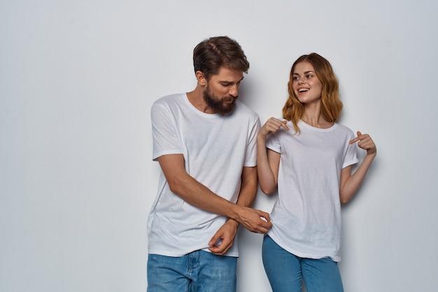 Jeune couple t-shirts blancs style de vie amusant posant la communication