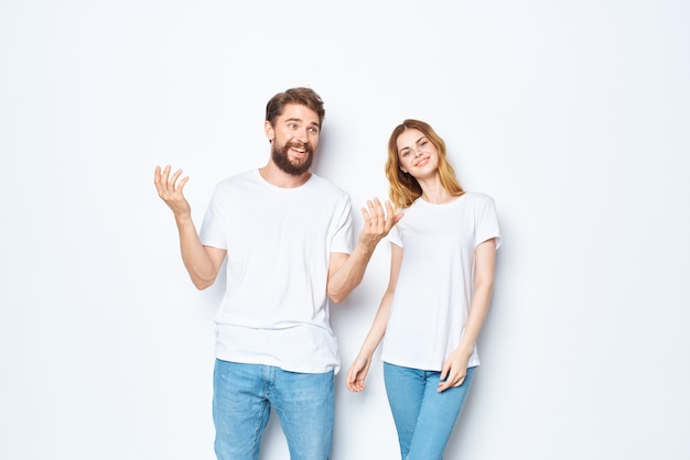 Jeune couple en t-shirts blancs vêtements de communication jeans fond clair
