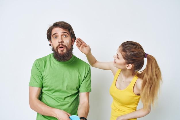 Jeune couple en t-shirts multicolores rasage soins de la peau du visage