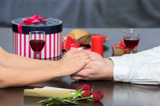 Jeune couple à la table de fête, tenant par la main