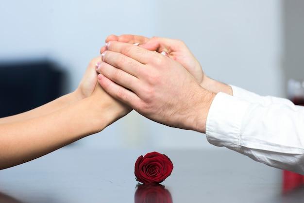 Jeune couple, à, table, à, rose, tenant mains