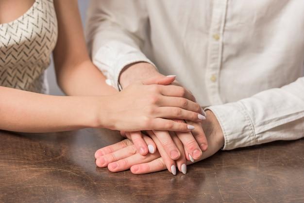 Jeune couple, à, table, tenant mains