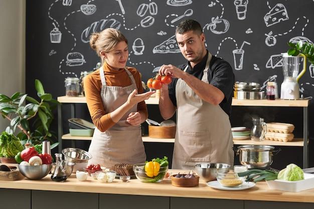 Jeune couple en tabliers examinant les tomates fraîches tout en se tenant près de la table et en préparant la nourriture en équipe dans la cuisine