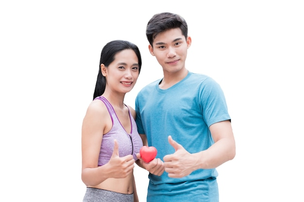 Jeune couple tenant articulation rouge maquette coeur avec pose pouces vers le haut. isolé sur fond blanc