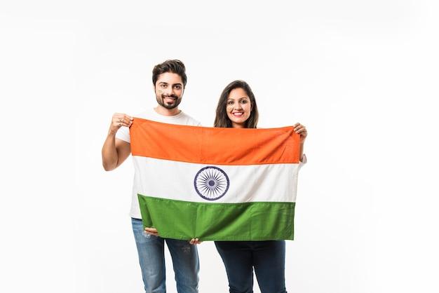 Jeune couple tenant un drapeau indien le jour de l'indépendance ou de la république, isolé sur fond blanc. mise au point sélective
