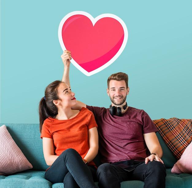 Jeune couple tenant une émoticône coeur