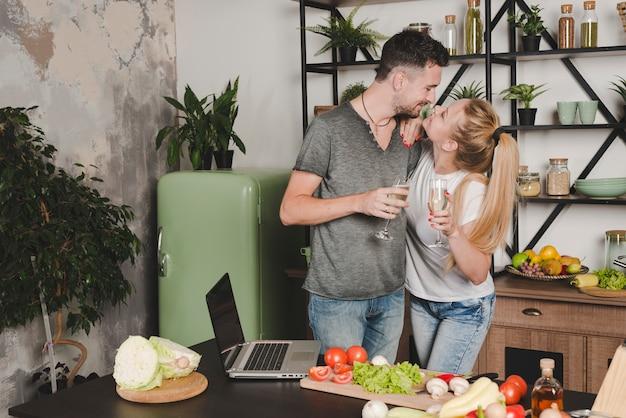Jeune couple tenant une flûte à champagne debout derrière le comptoir de la cuisine
