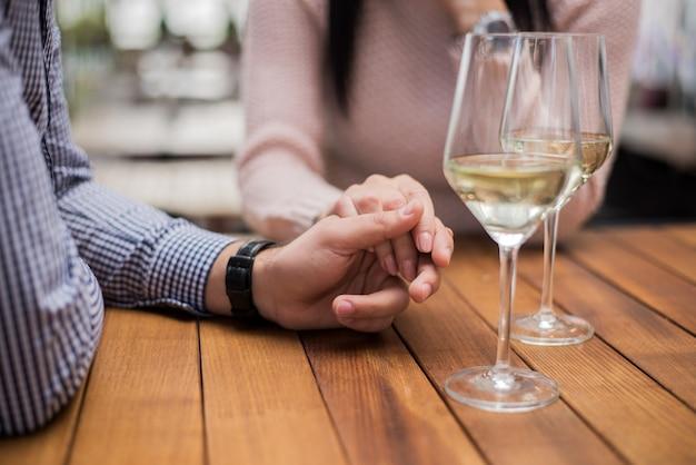 Jeune couple, tenant mains, à, les, café, gros plan