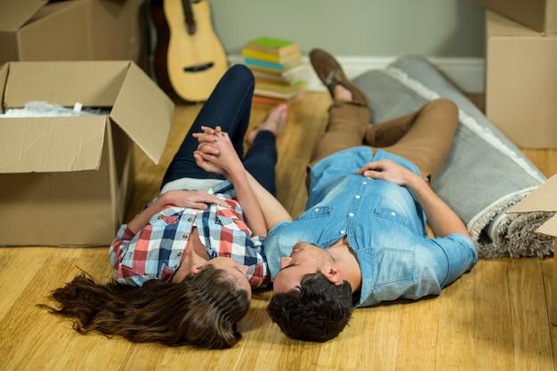 Jeune couple, tenant mains, et, coucher plancher, dans, leur, nouvelle maison