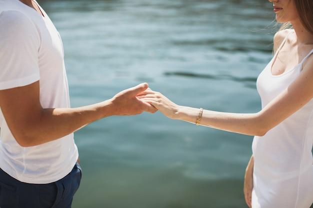 Jeune couple, tenant mains, plage