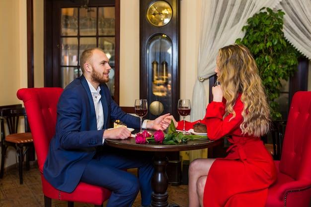 Jeune couple, tenant mains, à, table bois