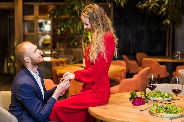 Jeune couple, tenant mains, à, table, dans, restaurant