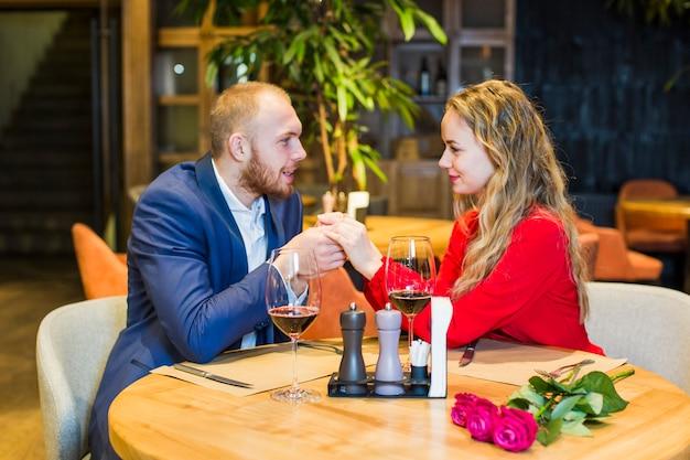 Jeune couple, tenant mains, à, table