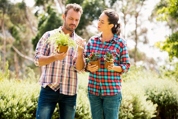 Jeune couple tenant des plantes en pot