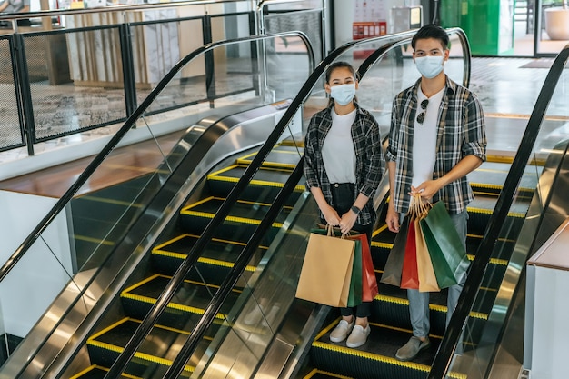 Jeune couple tenant plusieurs sacs en papier