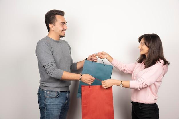 Jeune couple tenant des sacs à provisions ensemble.