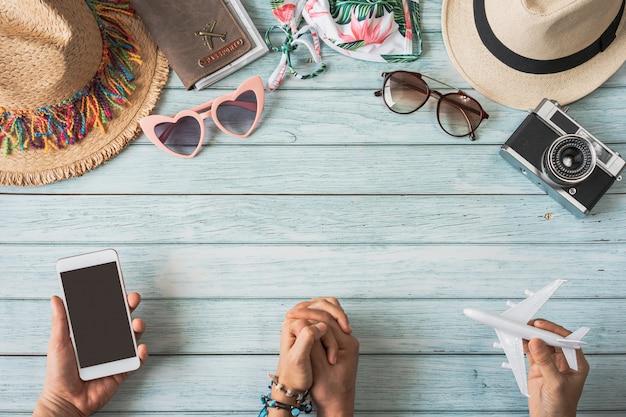 Jeune couple tenant un smartphone à écran vide avec des accessoires d'été de voyage et des articles sur fond de bois