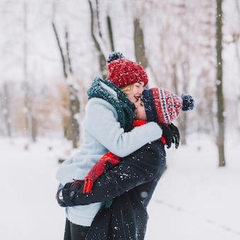 Jeune couple tendre embrassant dans les chutes de neige