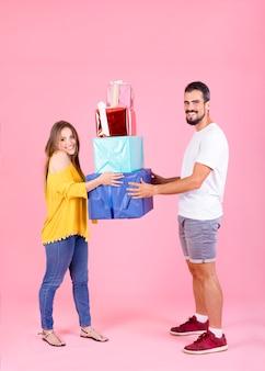 Jeune couple, tenue, coloré, boîtes cadeau, contre, toile de fond rose