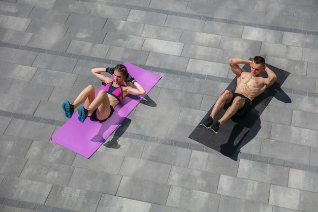Jeune couple en tenue de sport faisant l'entraînement du matin à l'extérieur